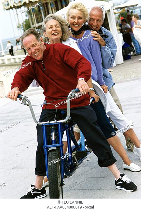 Mature men and women on stationary tandem bike, portrait