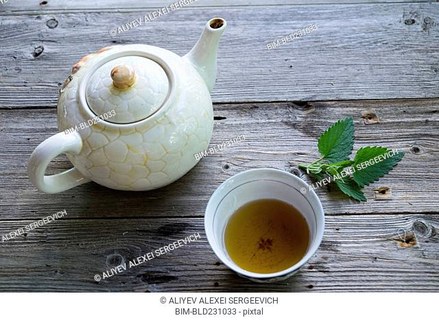 Cup of green tea with mint leaf and teapot
