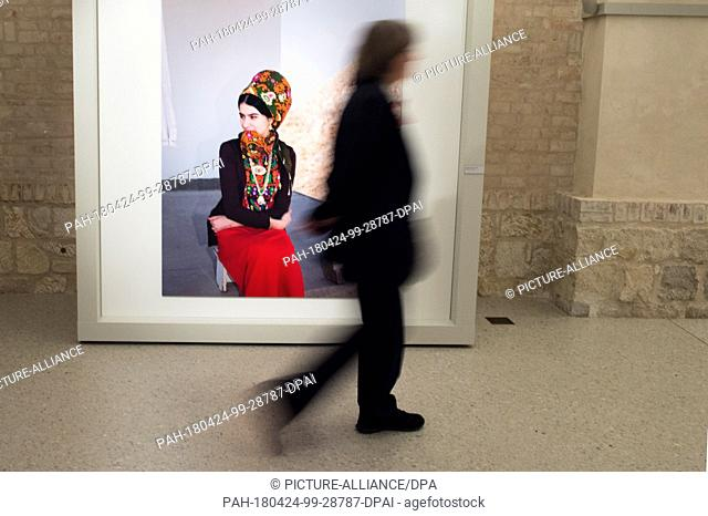 24 April 2018, Germany, Berlin: A visitor walks past an exhibited photo taken by photographer Herlinde Koelbl at the exhibition 'Margiana