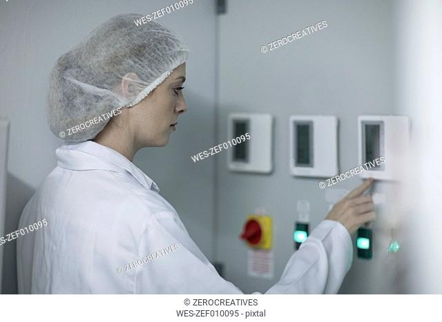 Woman in protective workwear operating machine