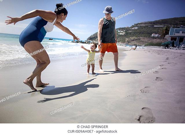 Toddler and grandparents playing on beach