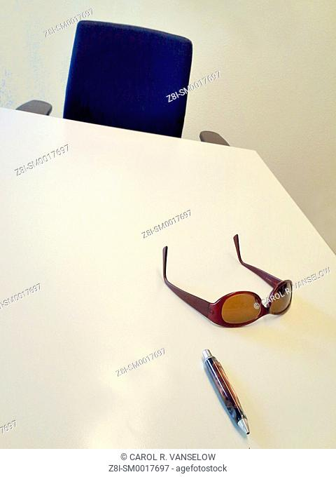 Sunglasses and pen lying on white desk with blue chair in background