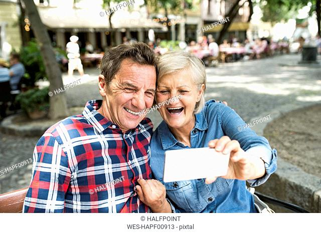 Laughing senior couple taking selfie with smartphone