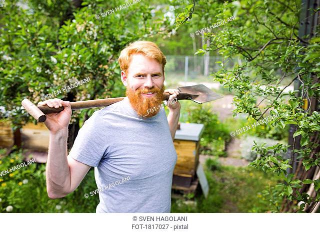 Portrait confident, smiling man with shovel in garden