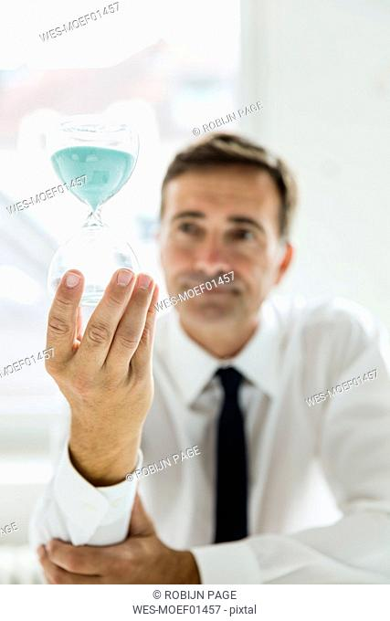 Serious businessman looking at hourglass in office