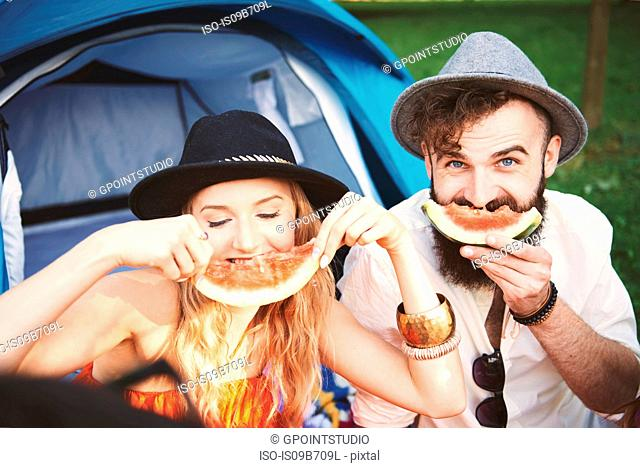 Young couple in trilbies making smiley face with melon slice at festival
