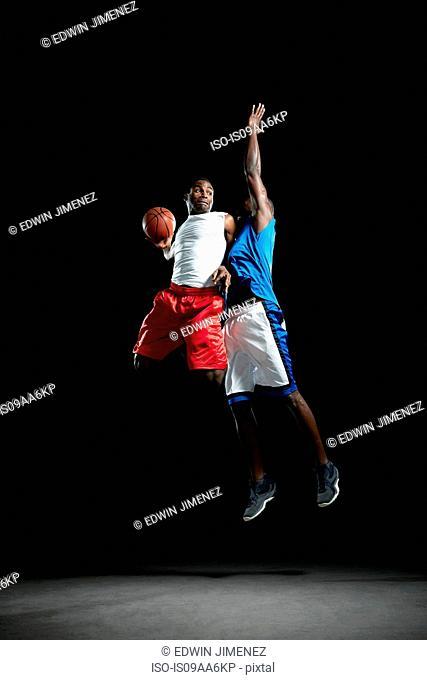 Male basketball players jumping