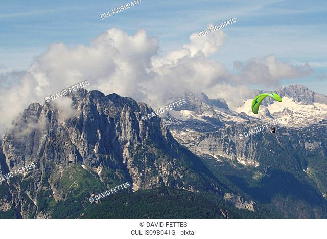 Lone paraglider paragliding in snow capped Julian Alps, Bovec, Slovakia
