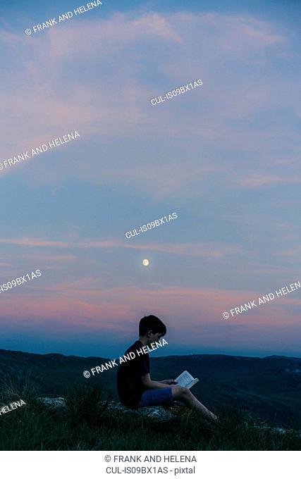 Boy reading book on hilltop, Snowdonia, Llanberis, Gwynedd, UK