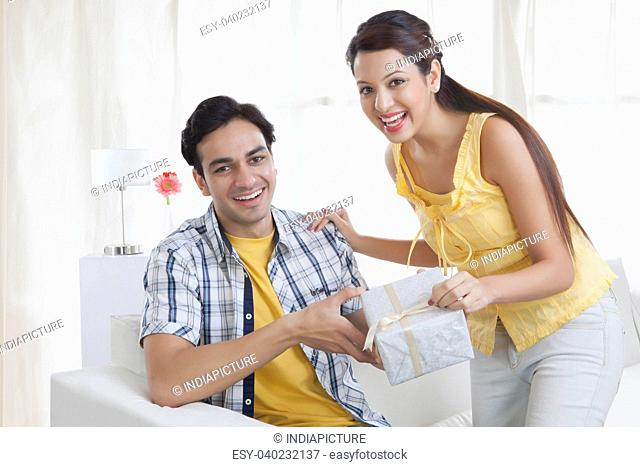 Portrait of a young couple with a gift box