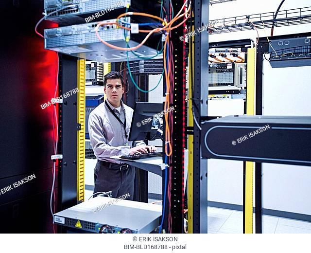 Hispanic technician using computer in server room