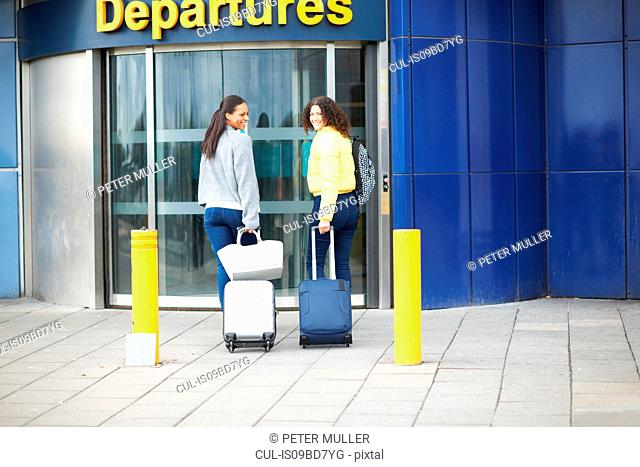 Women pulling wheeled suitcases to airport terminal, looking over shoulder smiling