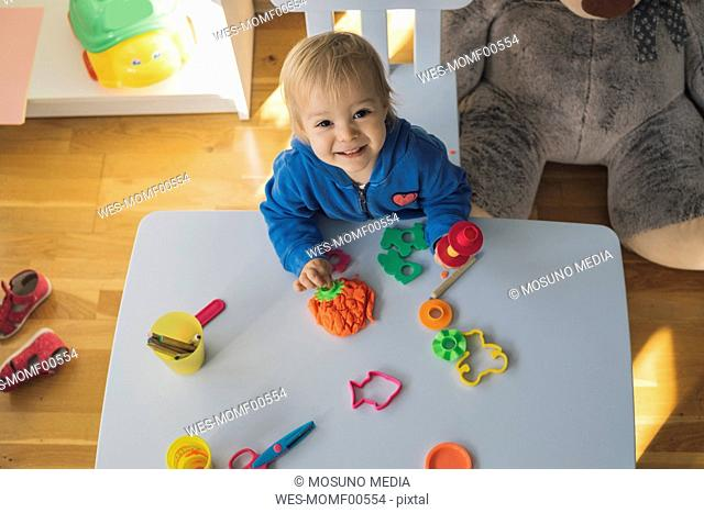 Portrait of smiling baby girl playing with modeling clay in children's room