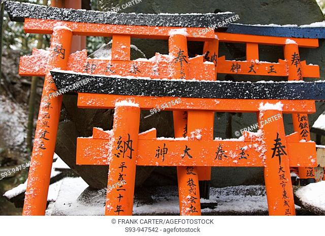 A view of the many small orange-red gates tori that are left as offerings at Fushimi-Inari-taisha shrine in Kyoto