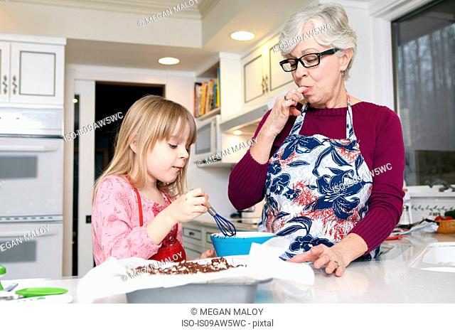Girl mixing cake at kitchen counter whilst grandmother licking her fingers