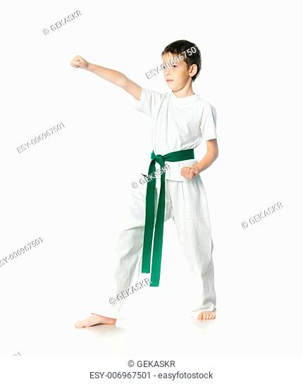 Young boy in kimono with green belt practising on a white background