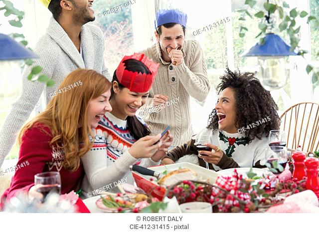 Laughing friends wearing paper crowns at Christmas dinner