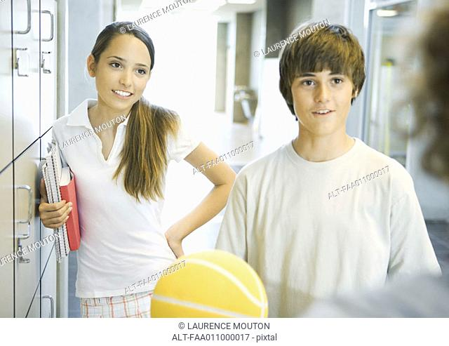 Young teens standing near school lockers