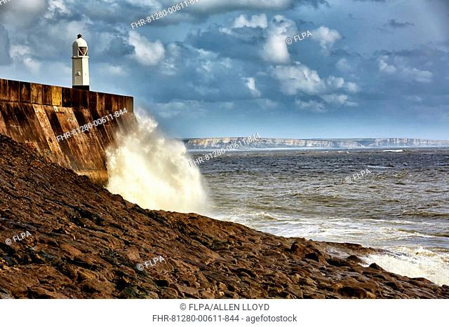 Waves crashing against coastal resort town seafront and lighthouse, Porthcawl Pier, Porthcawl, Bristol Channel, Glamorgan, South Wales, Wales, October