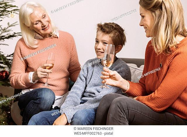 Mother and grandmother talking to grandson by Christmas tree