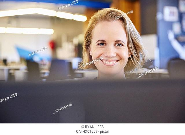Portrait smiling businesswoman working at computer