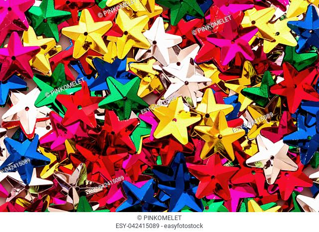 Shiny colorful sequins of star shape as festive party texture background