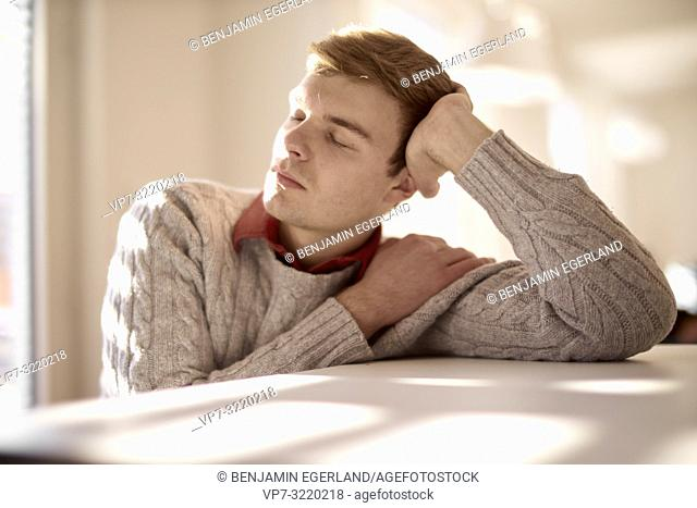 Young man sitting at table with closed eyes, looking to side, indoors, student, business man