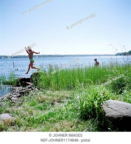 Girl jumping over rock on riverbank