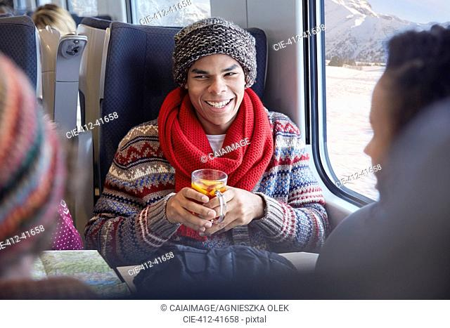 Smiling young man drinking mulled wine on passenger train