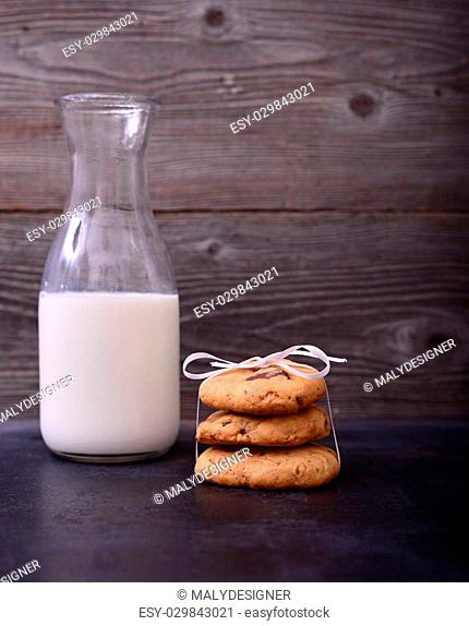 Stack of Chocolate chip cookie and bottle of milk on black background