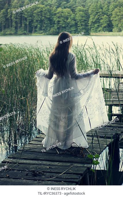 A young long-haired woman in an old-fashion wedding dress standing on an old pier