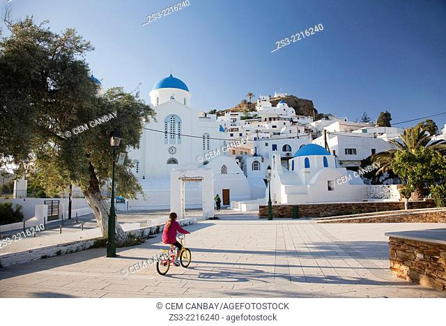 Girl riding a bike near a typical Cyclades church, a blue domed white Byzantine Greek Orthodox Chapel of Panaghia Gremiotissa in Chora, Ios, Cyclades Islands