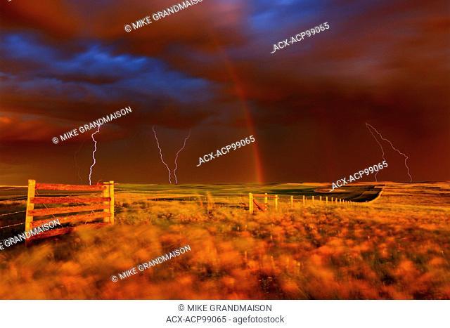 Lightning strikes, rainbow and setting sun during prairie storm. West Block Grasslands National Park Saskacthewan Canada