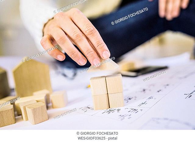 Woman placing building brick house on blueprint