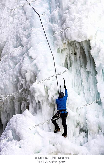 Ice climber with ice pick climbing frozen cliff face; Banff, Alberta, Canada