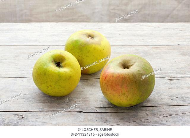 Three organic Benheimer apples on a wooden surface