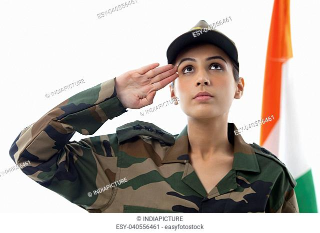 Female soldier saluting while looking up and Indian flag in background