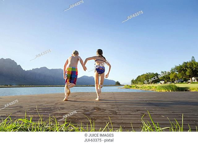 Children in swimwear, running to jump into a lake from a jetty