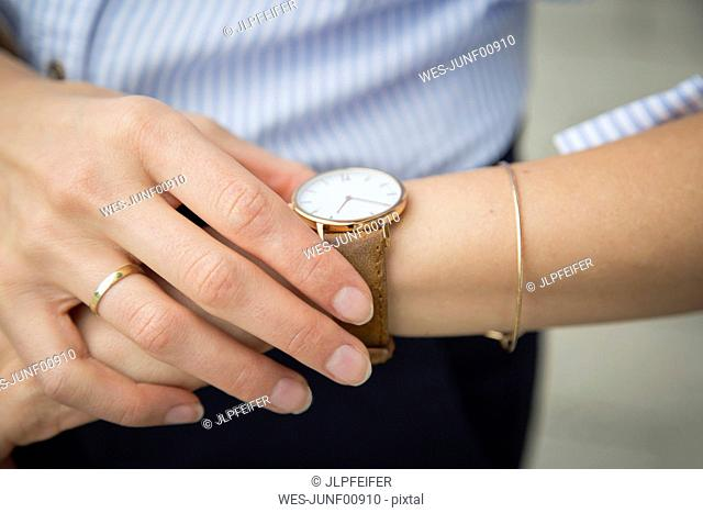 Businesswoman wearing wrist watch, close-up