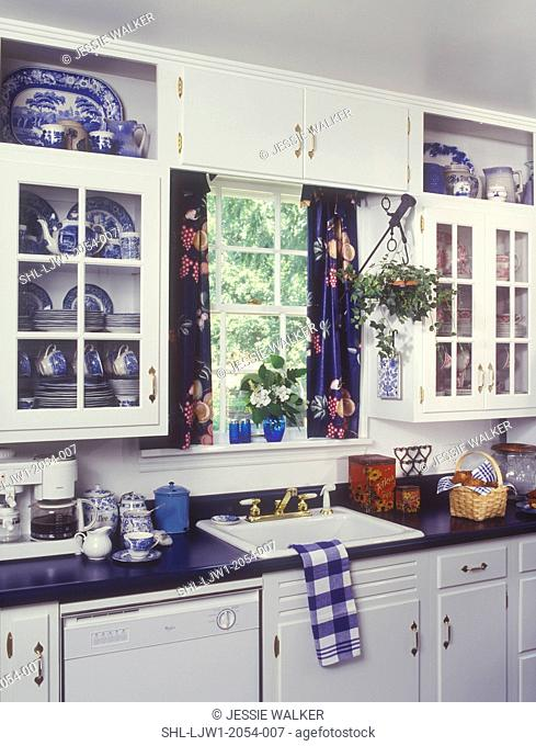 KITCHENS - White cabinets, blue laminate counter top, Sink area, window, with blue curtains, Blue Willow pattern china in cupboards, display shelves