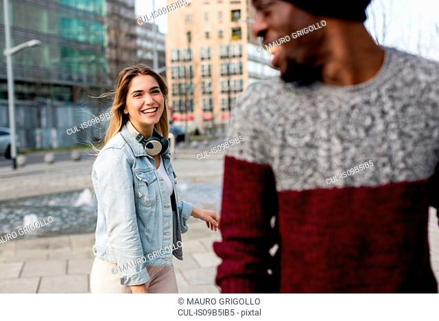 Young man and woman outdoors, laughing, man looking over shoulder at woman