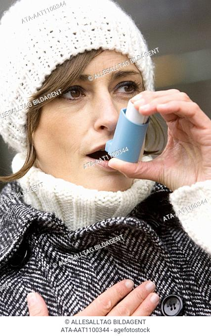 Woman with asthma inhaler