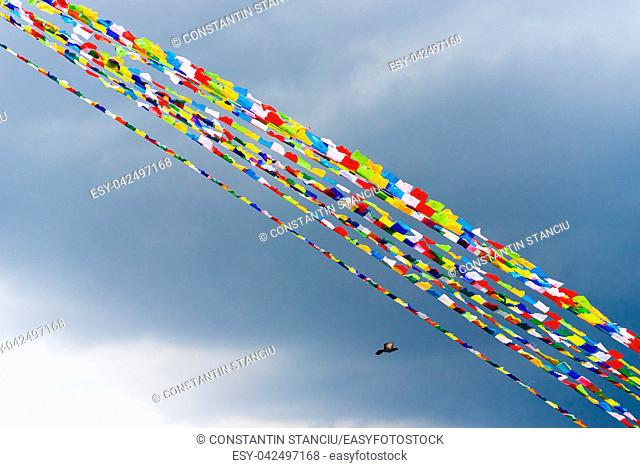 Traditional buddhist prayer flags over blue sky background, are used to bless the surrounding countryside and to promote peace, compassion, strength, and wisdom