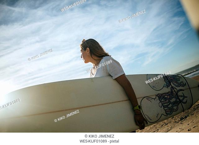 Young woman with surfboard on the beach by sunset