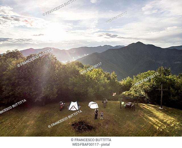 Italy, Tuscany, Pistoia, father and son on a meadow next to tent and motorbike