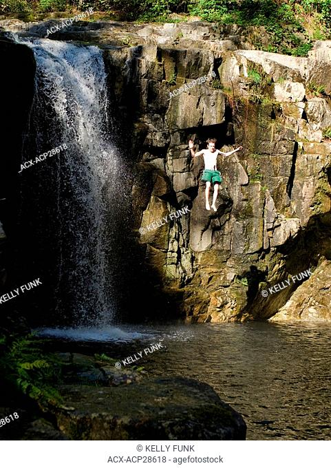 A young man jumps off the edge of Eagle Falls, near Powell River on the upper Sunshine Coast in the Vancouver coast and mountain region of British Columbia