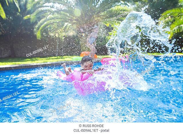Girl and boy splashing around in garden swimming pool