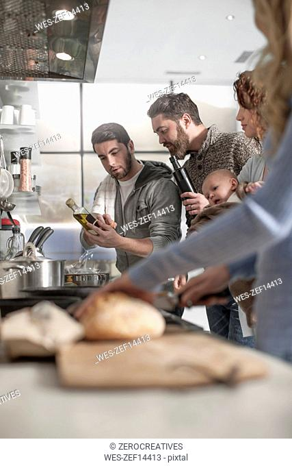 Family and friends preparing a meal in kitchen