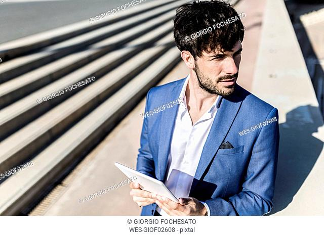 Young businessman holding tablet outdoors