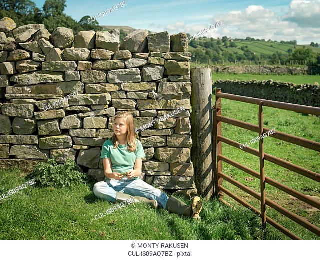 Teenage girl sitting by dry stone wall in field